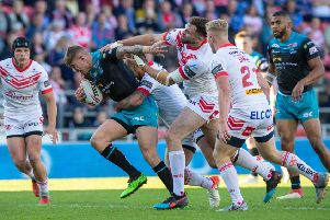 OUTNUMBERED: Liam Sutcliffe is hunted down by St Helens in last night's 36-10 defeat which has left Leeds Rhinos second-bottom in Super League though interim coach Richard Agar insists the mood is pretty good. Picture: Bruce Rollinson.