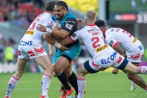 Leeds Rhinos' Konrad Hurrell is stopped by Louie McCarthy-Scarsbrook and Aaron Smith in Friday night's 36-10 loss at St Helens which leaves Leeds second-bottom. Picture by Bruce Rollinson.