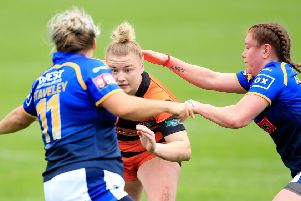 Castleford's Georgia Roche tackled by Leeds' Aimee Staveley and Dannielle Anderson.