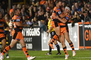 Castleford Tigers' Paul McShane leaps on Jake Trueman after his team-mate scores his hat-trick try against Hull FC. (PIC: JONATHAN GAWTHORPE)