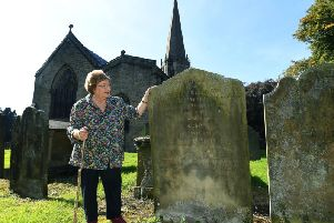 Family historian Denny Gibson has discovered a link between Boris Johnson and Jeremy Corbyn, whose ancestors both lived in Masham in the early 1800s. Pictured in the church yard of The Church of St Mary the Virgin, Masham, looking at a headstone belonging to Thomas and Ellen Stott, the great-great-grandparents of Jeremy Corbyn. Picture: Jonathan Gawthorpe