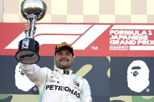 Winner: Mercedes driver Valtteri Bottas raises his trophy on the podium after winning the Japanese Grand Prix at Suzuka.