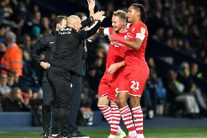 Cauley Woodrow celebrates his second goal at West Brom with Toby Sibbick and Barnsley caretaker manager Adam Murray.