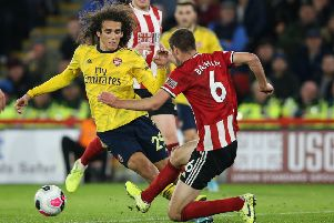 In the thick of it: Chris Basham tackles Arsenal's Matteo Guendouzi.