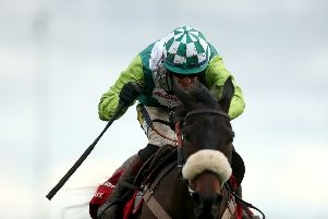 Clan Des Obeaux ridden by jockey Sam Twiston-Davies goes onto win the Ladbrokes King George VI Chase during day one of the Winter Festival at Kempton Park.