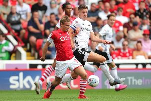 Barnsley's Luke Thomas, left, and Fulham's Tom Cairney, right, battle for the ball on the opening day of the season. Picture: Richard Sellers/PA