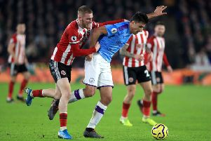 Sheffield United's Oliver McBurnie (left) and Manchester City's Rodri battle for the ball.