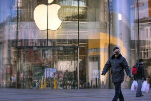 People wearing face masks walk past an Apple store in Beijing that was closed along with all its others in China. PIC: PA
