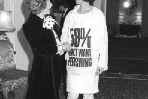 Prime Minister Margaret Thatcher greets fashion designer Katharine Hamnett, wearing a t-shirt with a nuclear missile protest message, at 10 Downing Street, where she hosted a reception for British Fashion Week designers.