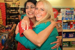Deana Sampson hugs post mistress Balwinder Dhillon, who sold her the winning ticket all those years ago