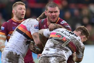 Batley's James Brown is tackled by the Bradford defence.