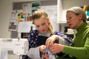 Emma Garry helps a pupil at her sewing class in Ilkley