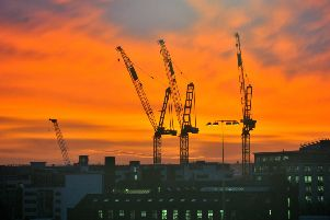 Work cranes silhouetted against a spectacular sunrise in the centre of Leeds. Picture Gerard Binks