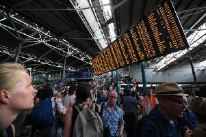 Commuters waiting at the boards in Leeds Station.