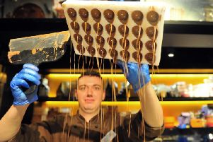 Chocolatier  Sam Flanagan   seen through the chocolate rain as he makes chocolates  at the York Chocolate Story  where a new exhibition 'Breaking The Mould :the Story of Kitkat'  is  being held.