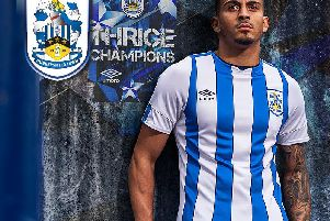 Karlan Grant models the new, sponsor-free, shirt that Huddersfield Town will wear this season