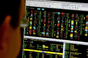 Office worker looks at a screen showing trading on the FTSE 100 index. Photo credit should read: PA Wire
