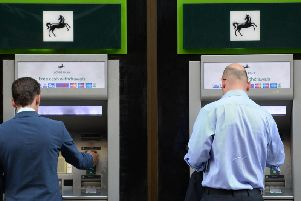 Bank customers use a cash machine. A committee of MPs has called for Minister to force banks to keep a branch open in every UK town.