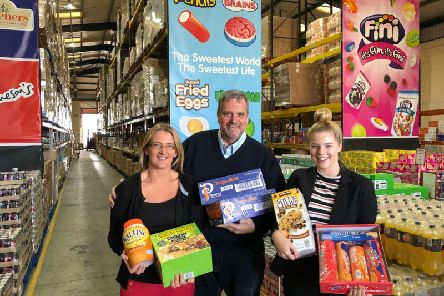 Andy Needham of Approved Food hands over donations to Lisa Bottomley and Ellena Roberts from the Huddersfield Town Foundation.