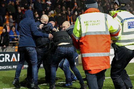 Two Blackpool supporters confronted a Fleetwood fan that had invaded the pitch