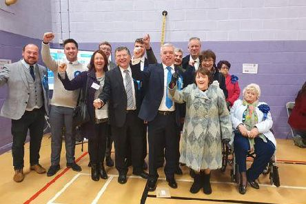 Mark Menzies celebrates his victory with party workers