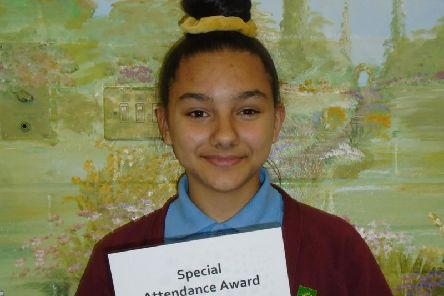 A proud Zahra shows off the award she received for attaining seven years of 100 per cent attendance at her school.