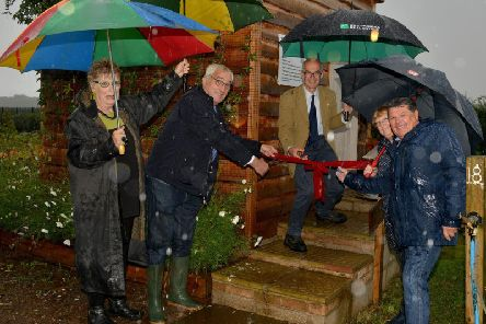 Braving the rain to cut the ribbon are Coun John Handley, Eddie Peat, of Four Winds Energy Co-operative and Coun Kevin Greaves watched by managing director Jennie Street and Board Director Kath Sharpe