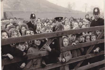 Children in a scene from Whistle Down The Wond jostling in silence to get a glimpse of 'the man'