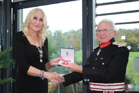 Jacci Woodcock receives her MBE in a ceremony by HM Lord-Lieutenant of Derbyshire,  William Tucker.