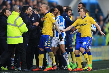 Tempers flare on the touchline as Huddersfield Town manager David Wagner (left) and Leeds United's Pontus Jansson (centre) confront each other. Picture: Nigel French/PA