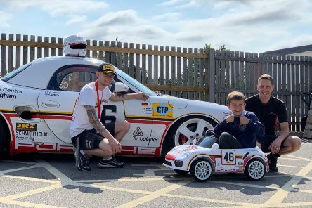 Robbie Brown and Wayne Minogue, of Porsche, with the cars and a youngster at the school.