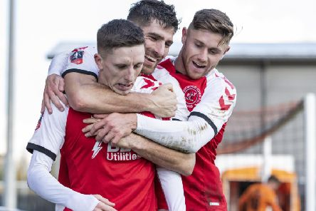 Fleetwood Twon celebrate as Ash Hunter (left) wraps up victory with their second goal at Barnet