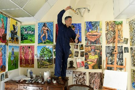 Anthony in his studio with works featuring in his new exhibition