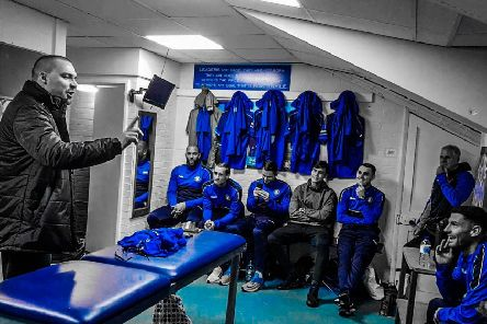 A scene from the video as songwriter Ben Spurr raps to Trinity players in the dressing room.