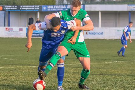 Frickley Athletic striker Ant Wilson stays strong in the tackle to fend off a Lincoln defender. Picture: Onion Bag Photos