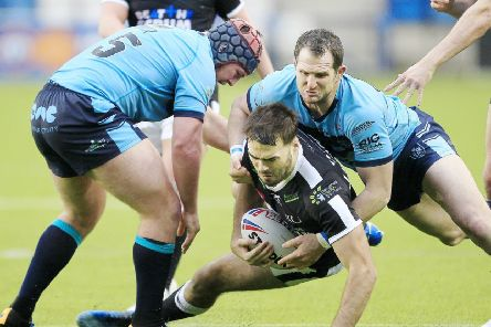 Widnes's Jay Chapelhow tackled by Featherstone's Luke Cooper and James Lockwood. Picture: Chris Mangnall/SWpix.com