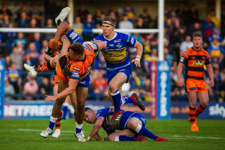 Castleford Tigers' Greg Eden is upended by Kallum Watkins in the game at Leeds. Picture: James Heaton