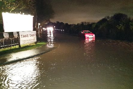 A car tries in vain to negotiate Moor Road at the height of the flooding.