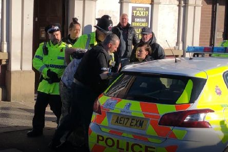 A man is bundled away by police to protect him from the angry after he disrupted a silent tribute with fireworks at a Remembrance Sunday event