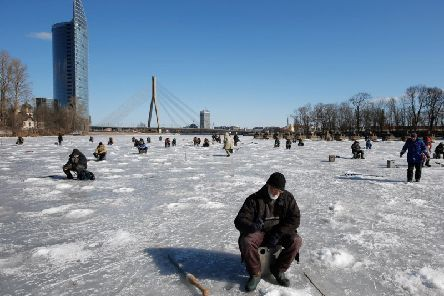 A general view of fishermen on the frozen ice of the Daugava River with the Shroud Bridge or Vansu tilts in the background on March 22, 2013 in Riga, Latvia. (Photo by Dean Mouhtaropoulos/Getty Images)