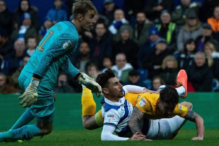 Preston striker Sean Maguire is thwarted by a sliding challenge from QPR skipper Grant Hall