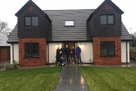 Andrew Bradshaw (centre) at the house he is offering up with some of the builders and Kirsty Cropper and Liam Batty (front left), who will be shifting through applications