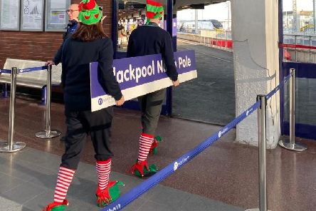Northerns elves carry the new sign into Blackpool North Pole station