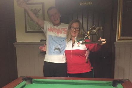 Winners of the 2019 Stevie Dawes Pool Tournament, Alan Ogden and Marion Canny, with their trophies, which reflect Stevies other sporting passion, horse racing