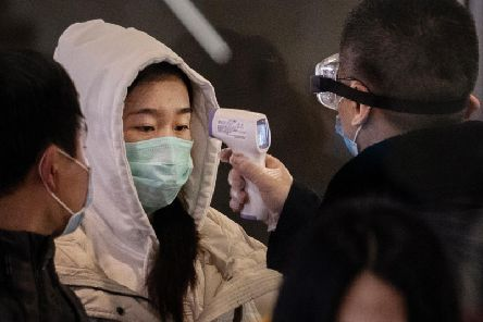 A Chinese passenger that just arrived on the last bullet train from Wuhan to Beijing is checked for a fever by a health worker at a Beijing railway station on January 23, 2020 in Beijing, China (Photo by Kevin Frayer/Getty Images)