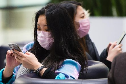 People wear masks following the outbreak of a new virus as people arrive from the International terminal at Toronto Pearson International Airport in Toronto on Saturday, Jan. 25, 2020.
