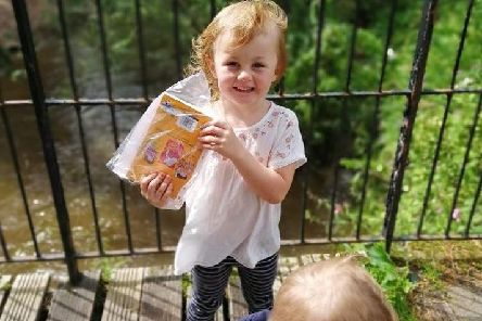 Happy four-year-old Harriet Ormerod proudly shows off a book she found in Haslam Park