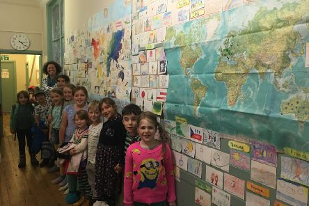 Pupils from Lancaster Steiner School with their wall display showing hundreds of cards from Steiner schools around the world.