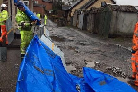 Workers deploy temporary barriers in case of more flooding. (Photo Environment Agency).