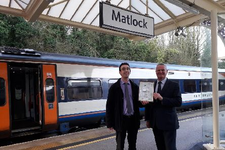 Coun Trevor Ainsworth (right) and Alastair Morley, the county council's community rail officer, show off the accreditation certificate at Matlock station.